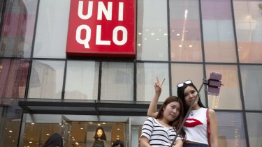 Women take a selfie outside the Uniqlo store in Beijing where a steamy video purportedly taken inside one of its fitting room showing a couple apparently having sex was filmed.