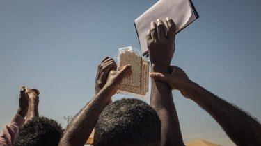 Eritrean and Sudanese asylum seekers hold matzot - traditional Jewish bread - during a celebration of Passover organised by Israeli activists outside the Holot detention centre.