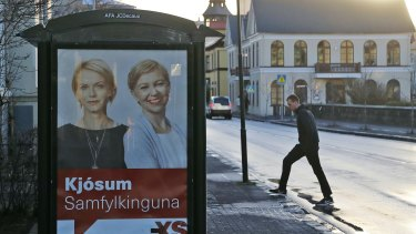 A man walks near a social democrats election poster in Reykjavik.