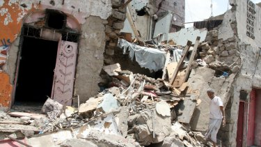 A man walks on the rubble of a house destroyed during recent fighting in Taiz.