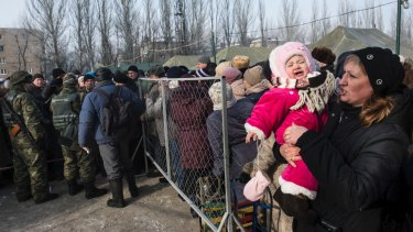A baby girl cries in her mother's arms as they stand in queue to get humanitarian aid in Avdiivka, eastern Ukraine.