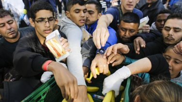 Migrants grab for food at a reception centre for refugees and asylum seekers in Berlin.
