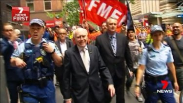 Former prime minister John Howard is escorted by police in Sydney.