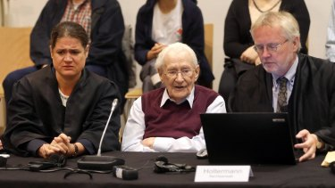 94-year-old former SS sergeant Oskar Groening sits between his lawyers Hans Holtermann, right, and Susanne Frangenberg, left, during the verdict of his trial.