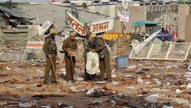 Cleaning up: Policemen collect belongings left behind after people left the ashram.