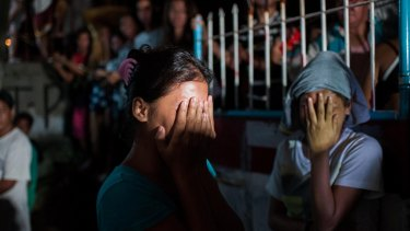 Two women await the fate of their loved ones during an alleged police drug raid on a suspected drug den in Manila.
