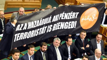 "Members of the far-right opposition Jobbik party hold a banner which reads: ""The traitor is the one who lets the terrorist in for money!"", complete with pseudo-Arabic script, during the vote."