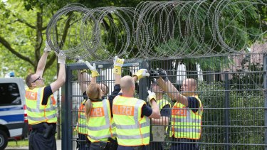 Police officers fix barbed wire on to a fence at the Sternstanze train station close in Hamburg.