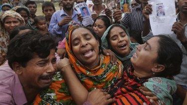 Bangladeshi relatives of garment worker Mohammed Abdullah  arrive to collect his body at a makeshift morgue after the Rana Plaza collapse in April 2013.