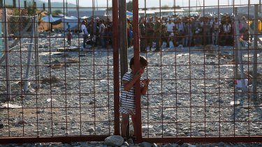 A young Iraqi boy slips through a narrow opening in a gate inside a camp used for temporary detention of migrants shortly after they crossed the Macedonian border from Greece.