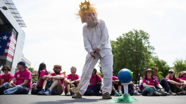 A demonstrator dressed as King Trump prepares to swing a golf club at the Earth during the People's Climate Movement March in Washington.