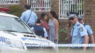 Police and family, including the boy's grandmother (in the red top), outside the house.