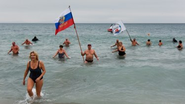 Crimean people wave a Russian national flag celebrating Orthodox Christmas in the Black Sea in Yevpatoriya earlier this year.