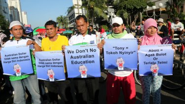 Indonesians hold posters aimed at Tony Abbott during protests in Jakarta.