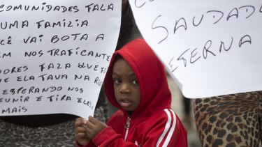 A boy stands between signs during a protest against violence, at the burial of Roseli dos Santos de Jesus killed by a stray bullet during a shooting between police and drug traffickers at a cemetery in Rio on Tuesday.