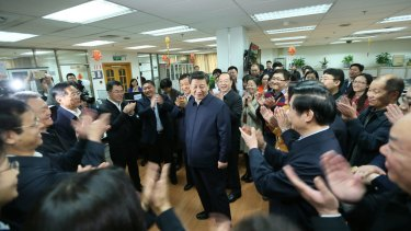 Workers applaud as Chinese President Xi Jinping, centre, talks with editors in the general newsroom of the People's Daily in Beijing on Friday.