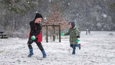 Jamie and Ryan Haworth play in the falling snow at Day's Picnic Area, Mount Macedon.