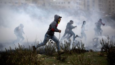 Palestinian protesters run for cover from tear gas fired by Israeli soldiers during clashes in Ramallah on Monday.
