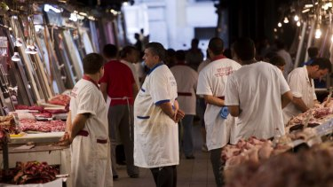 Butchers wait for clients in a meat market in central Athens on Tuesday.