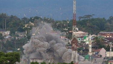 Debris fly as Philippine Air Force fighter jets bomb suspected locations of Muslim militants in Marawi on Friday.