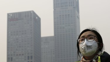 A woman wearing a face mask to protect herself from pollutants walks past office buildings shrouded with pollution haze in Beijing last December.