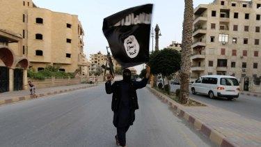 A jihadist holds an Islamic State flag held aloft in Raqqa, Syria.