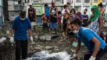 Morgue workers carry the unclaimed body of a victim of an extrajudicial killing in Manila, Philippines.