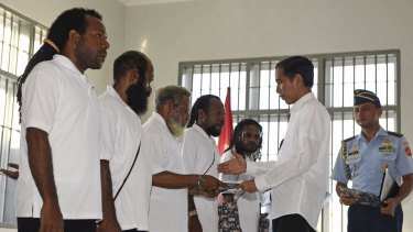 Indonesia's President Joko Widodo (right) hands over official pardons to five Papuan political prisoners belonging to the Free Papua Movement at a jail in Jayapura in May 2015.