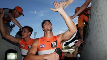 GWS Giants forwards Jonathon Patton and Rory Lobb celebrate with fans after victory against Geelong at Manuka Oval this year.