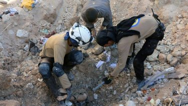 In reality: Members of Civil Defence removing a dead body from under the rubble after airstrikes hit in Aleppo last month.