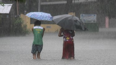 Residents wade across floodwaters caused by Typhoon Goni in Bacnotan, northern Philippines on Sunday.