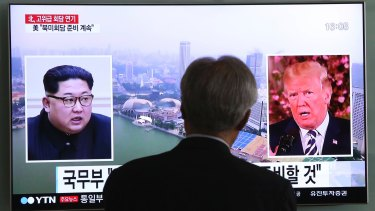 A man watches a TV screen in Seoul as the summit meeting in Singapore is previewed.