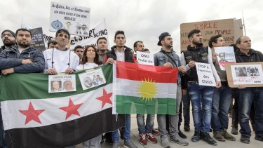 Protesters hold posters and flags during a demonstration against the Syrian regime during Syrian Peace talks in Geneva, Switzerland, on Friday.