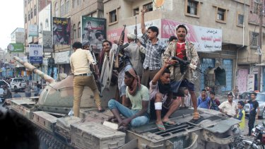 Militants loyal to Yemen's exiled government ride a tank they seized from Houthi militiamen in Taiz.