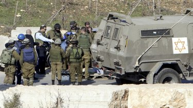 Israeli security forces stand at the scene of an alleged attack at Halhul checkpoint near Hebron, in the occupied West Bank,  after troops shot and killed a Palestinian man who allegedly attempted to ram his car into Israeli security forces.