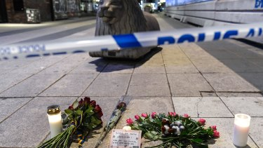Candles and flowers are placed near the site where a beer truck crashed into a department store in central Stockholm on Friday.