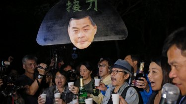 Pro-democracy protesters display a picture of Hong Kong chief Leung Chun-ying outside the Hong Kong Government House, as they celebrate on Saturday.