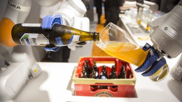 An industrial robotic arm pours a glass of beer at the Automatica trade fair in Munich on Tuesday.