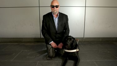 Vision-impaired man Mark Birkett with his guide dog Lester.