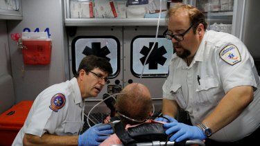 Ambulance medics John Gardner, left, and David Farmer care for a man in his 40s  found unresponsive after overdosing on an opioid in Boston. Nurses at the hospital recognised the man, saying he was brought in the day before also after overdosing.