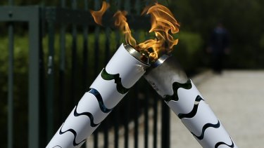 Torch alight: The Olympic flame is symbolically passed from one torch to another after after the official ceremonial lighting of the flame in Ancient Olympia, Greece.