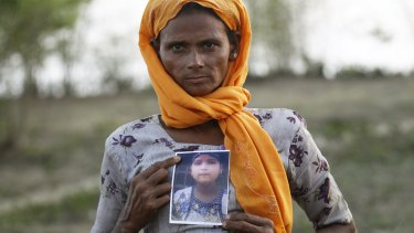 Rohiakar, a Rohingya Muslim woman, shows a picture of her daughter Saywar Nuyar, 22, who is being held by a human trafficker, at a refugee camp outside Sittwe, Myanmar.