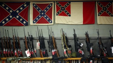 Confederate flags hang above various rifles for sale at the Knob Creek Machine Gun Shoot in Kentucky earlier this month.