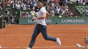 A fan runs towards Roger Federer following his win at the French Open.