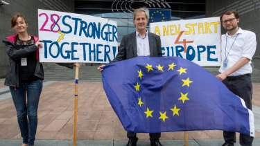 Jo Leinen, centre, a German member of the European Parliament, holds an EU flag outside the parliament in Brussels on Friday.