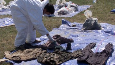A forensic expert working for the UN  war crimes tribunal set out clothes, for families to identify, from human remains found in a central Kosovo mass grave in 1999.