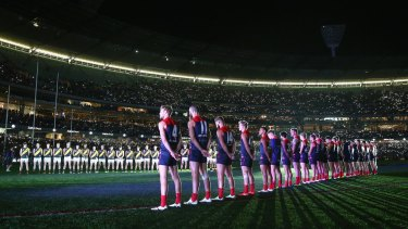 Melbourne and Richmond players line up for The Last Post at the MCG on Sunday night.