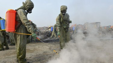 Soldiers from a People's Liberation Army chemical-defence unit work to neutralise sodium cyanide residue at the Tianjin blast site.