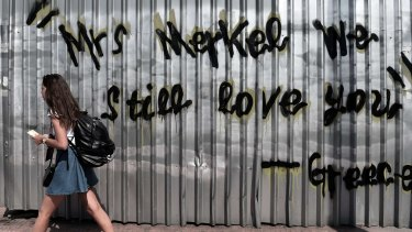 A young woman walks past a graffiti acknowledging Germany's role in propping up Greece.