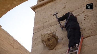A militant hammers away at a face on a wall in Hatra, a large fortified city recognised as a UNESCO World Heritage site, south-west of Mosul, Iraq, in this image from a militant video released in April 2015.